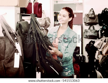 Portrait attractive teenager girl buying handbag in fashion shop