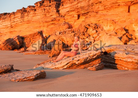 Portrait beautiful young blonde bikini woman relaxed with closed eyes at remote beach at sunset, rocky cliff coast as background and copy space.
