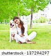 portrait Hispanic girl embracing her dog in the park on the background of the house - stock photo