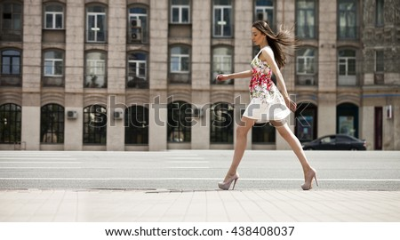Portrait in full growth, young beautiful brunette woman in white flowers dress walking on the street, summer outdoors