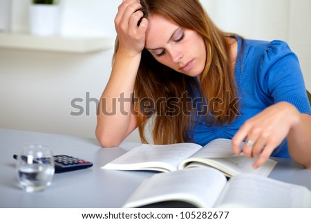 Portrait of a adult pretty student girl reading a book at study room