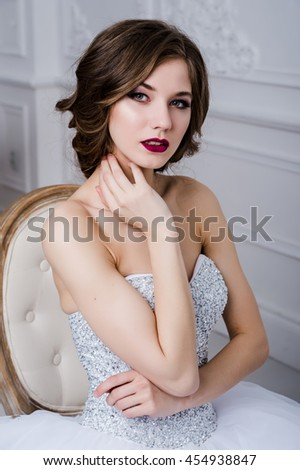 Portrait of a beautiful bride with bright makeup, red lips over luxury room interior, sitting on chair