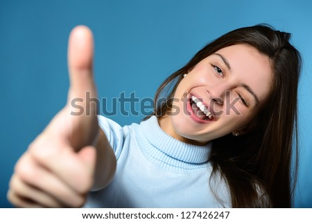 Portrait of a beautiful, confident and cheerful teenager girl showing thumbs up isolated on blue