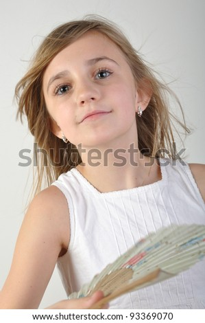 portrait of a beautiful elementary age girl fanning herself