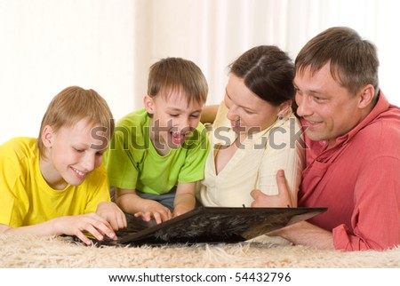 portrait of a beautiful family of four with a laptop