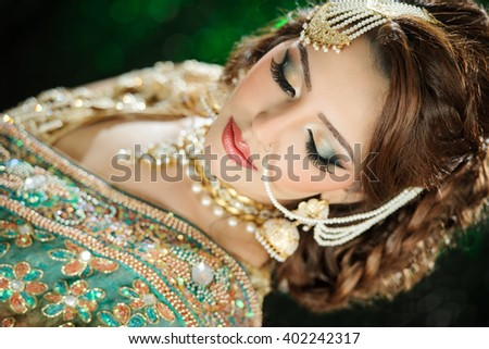 Portrait of a beautiful female model in traditional ethnic asian indian bridal costume with heavy makeup and jewellery