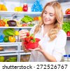 Portrait of a beautiful female standing near open fridge full of fruits and vegetables, eating fresh red ripe juicy strawberries, enjoying healthy nutrition, wellness and healthy living   - stock photo