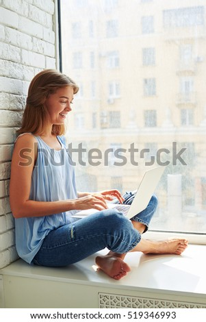Portrait of a beautiful girl sitting at home and working on a laptop isolated at home, with a view on a big busy city
