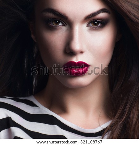 Portrait of a beautiful girl with bright makeup and red lipstick