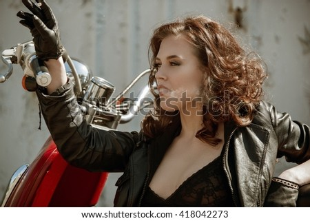 portrait of a beautiful girl with cigarette near retro motorcycle