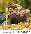 portrait of a beautiful happy family lying in autumn park - stock photo