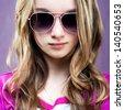 portrait of a beautiful little girl sunglasses on a purple  background - stock photo