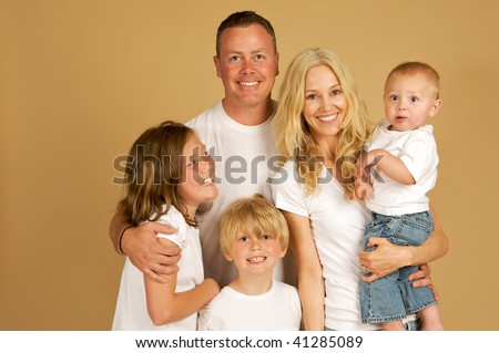 Portrait of a beautiful loving family of five all snuggled together in white tee shirts and jeans