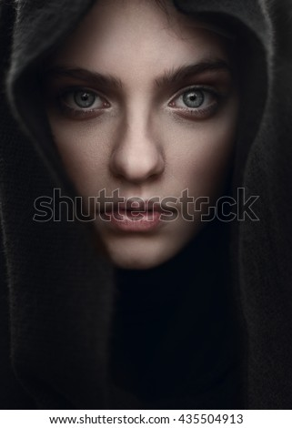 portrait of a beautiful mysterious girl in the hood closeup