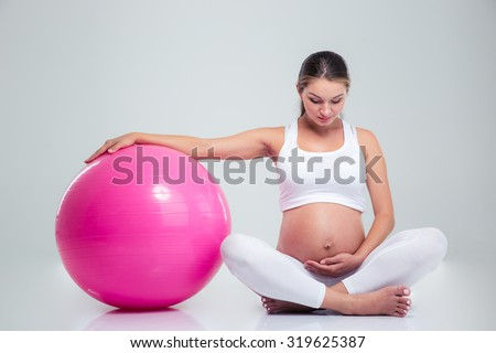 Closeup portrait pregnant woman holding alarm stock photo for Sitting on the floor during pregnancy