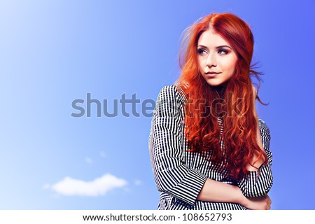 Portrait of a beautiful red-haired young woman over blue sky.