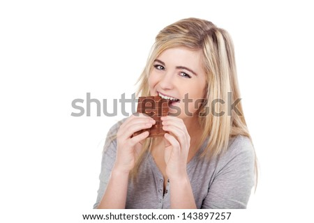 Portrait of a beautiful teenage girl eating chocolate against white background