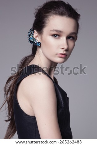 Portrait of a beautiful teenager girl with long curly hairs - isolated on grey background with necklace blue earring kaffa