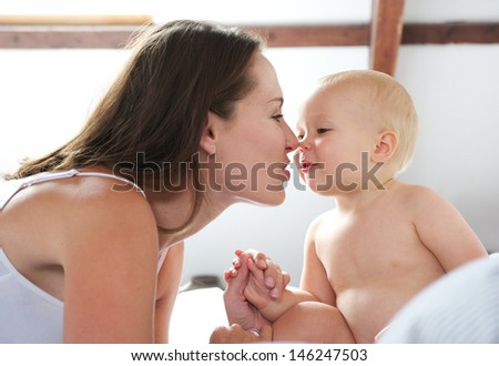 Portrait of a beautiful woman and baby playing on bed