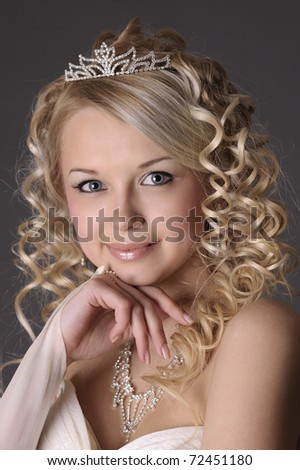 Portrait of a beautiful woman dressed as a bride over gray background.