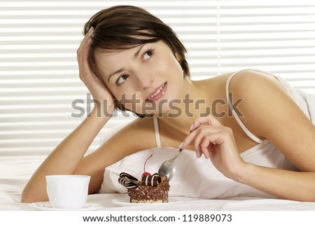 portrait of a beautiful woman eating cake on a bed