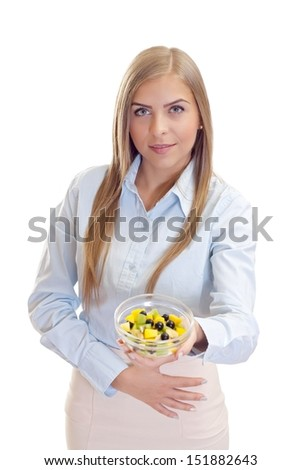 Portrait of a beautiful woman holding a bowl with  fruit salad