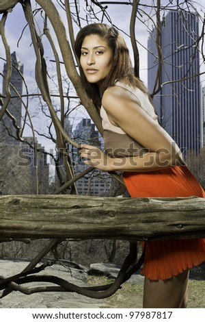 Portrait of a beautiful woman in a big city. The background is small woods, vine tree and high building skyline