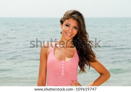Portrait of a beautiful woman with long pink dress on a tropical beach