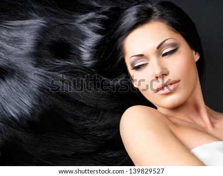 Portrait of a beautiful woman with long straight black hair lying on the dark background