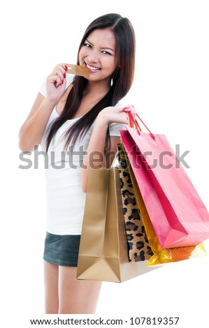 Portrait of a beautiful young Asian woman biting credit card and holding shopping bags over white background