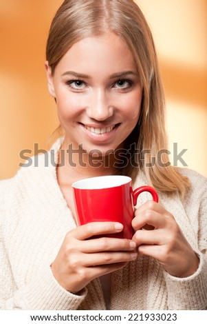 Portrait of a beautiful young blond holding cup of warm tea.