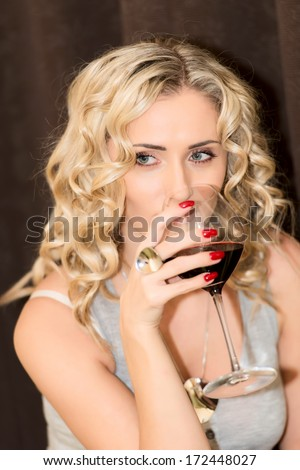 Portrait of a beautiful young blonde woman holding a glass of red wine