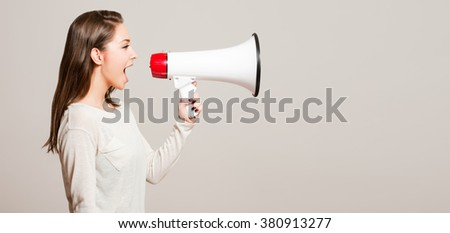 Portrait of a beautiful young brunette woman using loudspeaker.