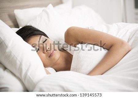 Portrait of a beautiful young Chinese female sleeping in bed at home