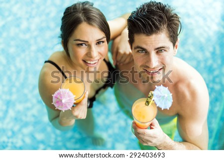 Portrait of a beautiful young couple smiling and drinking a cocktail in a pool