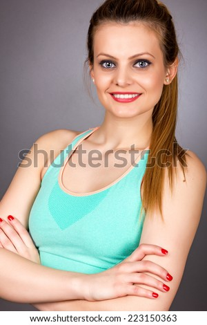 Portrait of a beautiful young fitness woman with arms folded isolated over gray background