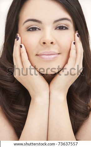 Portrait of a beautiful young Latina Hispanic woman resting on her hands and with an enigmatic smile