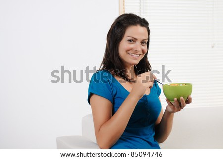 Portrait  of a beautiful young woman  having breakfast cereal  while smiling at the camera.