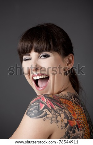 Portrait of a beautiful young woman with a tattoo on the backs winking eyes