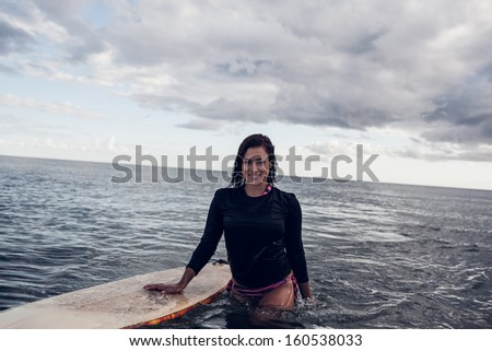 Portrait of a beautiful young woman with surfboard in the water at beach