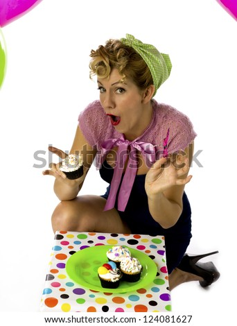 Portrait of a blonde woman holding a cupcake with mouth open while sitting over white background