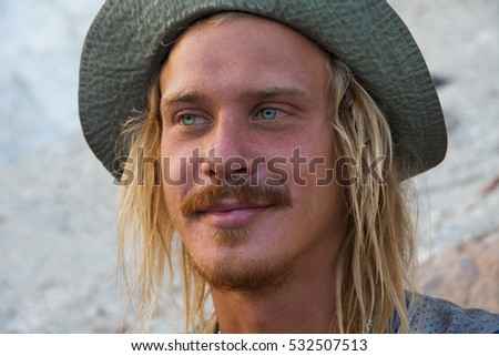 portrait of a blue eyed blond young man wearing a hat and a mustache