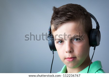 Portrait of a boy listening to music on headphones over grey background.