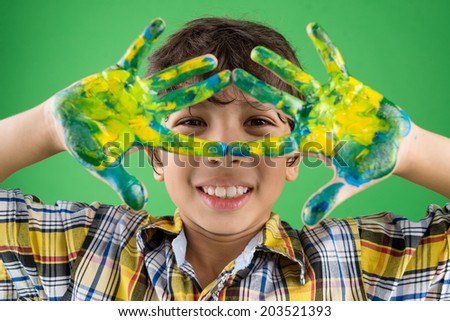Portrait of a boy showing his hands painted in different colors