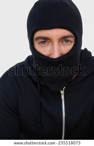 Portrait of a burglar with black jacket and balaclava on white background