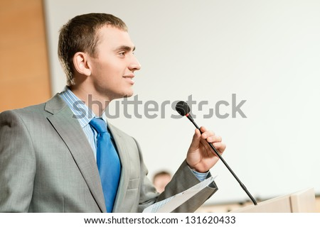 Portrait of a business man holding microphone on conference, speaks into the microphone and looks into the room