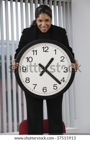 Portrait of a business woman standing on an office chair in a meeting and showing the deadline using a wall clock for emphasis.