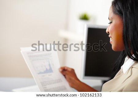 Portrait of a cheerful business woman reading documents