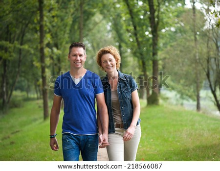 Portrait of a cheerful couple walking together in the woods