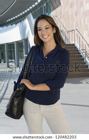 Portrait of a cheerful female executive with handbag standing in front of office building